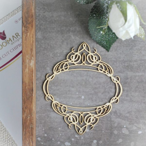 laser cut chipboard frame with decorative ornaments on the top and bottom